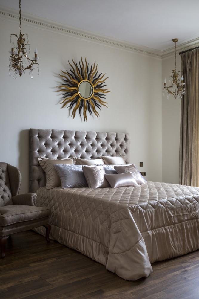 Интерьер этой спальни построен на оттенках и фактурах одного цвета - серо-бежевого. блестящие сатиновые и мягкие бархатные фактуры загадочно мерцают и переливаются в тусклом свете московского утра. Комната небольшая, поэтому здесь только необходимое - комод, кресло, кровать