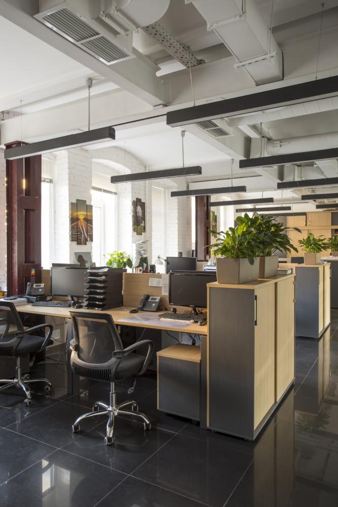 Ресепшен. Круглые формы стойки перекликаются с арочной формой потолка. Синяя контрастная стена с логотипом компании.