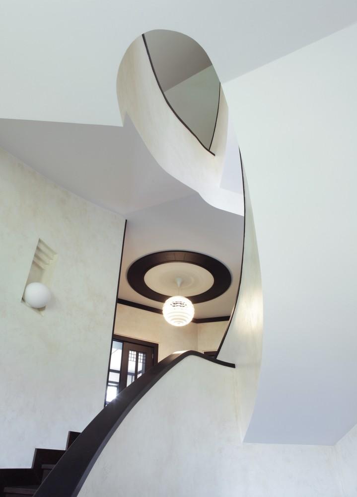 На второй этаж дома поднимается сложная спиралевидная лестница, выполненная в той же цветовой гармонии тёмных и светлых элементов. Лестница задаёт пространству пластику, близкую к тягучим линиям ар-нуво.